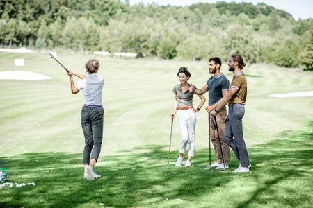 Photo pour Group of a young people dressed casually playing golf on the beautiful golf course on a sunny day - image libre de droit