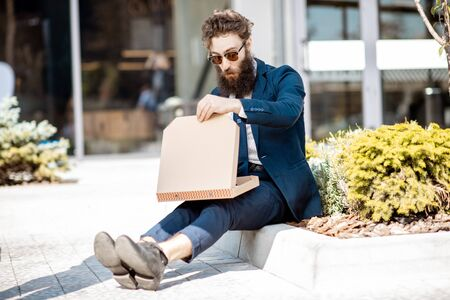 Foto de Hungry businessman dressed in the suit eating pizza while sitting on the street near the office building outdoors - Imagen libre de derechos