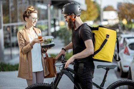 Foto per Courier delivering fresh lunches to a young business woman on a bicycle with thermal backpack. Takeaway restaurant food delivery concept - Immagine Royalty Free