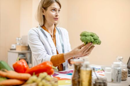 Photo pour Nutritionist holding fresh broccoli, working on a diet plan in the office - image libre de droit