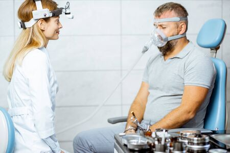 Photo pour Adult man during a medical breathing treatment with respiratory mask against snoring sitting with doctor at the ENT office - image libre de droit