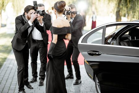 Photo pour Beautiful woman dressed in retro style as a famous movie actress arriving on the awards ceremony with photo reporters taking pictures of her - image libre de droit