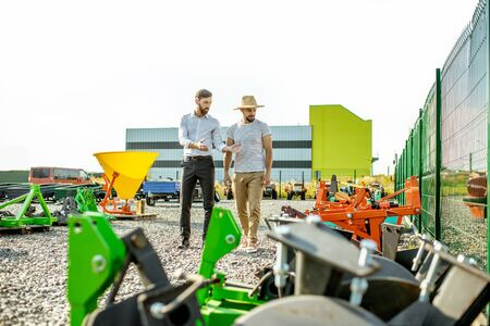 Photo for Young agronomist walking with salesman at the open ground of the shop with agricultural machinery, choosing new plow for tillage - Royalty Free Image