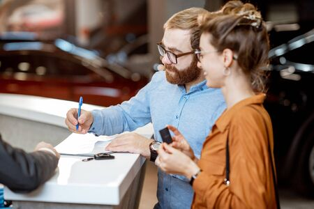 Photo pour Young couple signing some documents, buying a new car in the modern showroom of the car dealership - image libre de droit