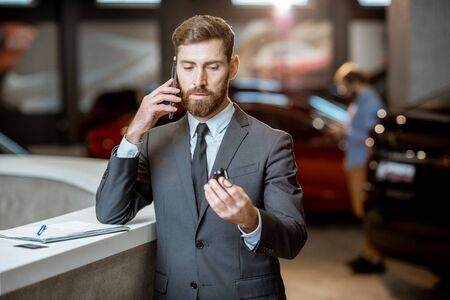 Photo pour Portrait of a happy sales manager or businessman talking with phone and feeling excited about selling or buying a new car - image libre de droit