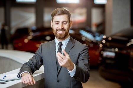 Photo pour Portrait of a happy sales manager or businessman holding car key, feeling excited about selling or buying a new car at the car dealership - image libre de droit
