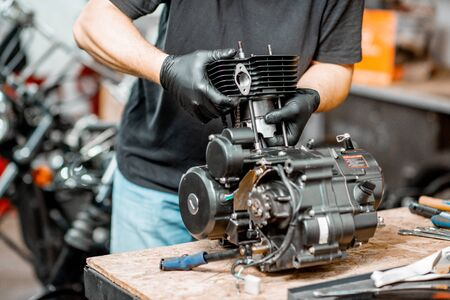 Photo pour Workman disassembling motorcycle engine during a repairment at the working table of the workshop, close-up with no face - image libre de droit
