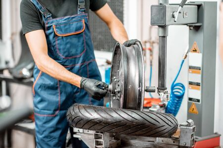 Photo for Service worker changing motorcycle tire on a special equipment for tire installation in the workshop, close-up with no face - Royalty Free Image