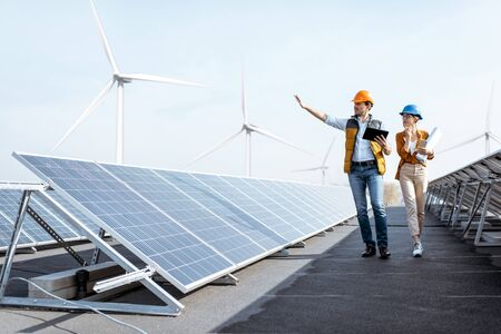 Foto de View on the rooftop solar power plant with two engineers walking and examining photovoltaic panels. Concept of alternative energy and its service - Imagen libre de derechos