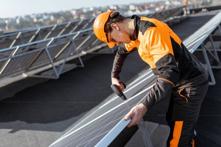 Photo for Well-equipped worker in protective orange clothing installing or replacing solar panel on a photovoltaic rooftop plant. Concept of maintenance and installation of solar stations - Royalty Free Image