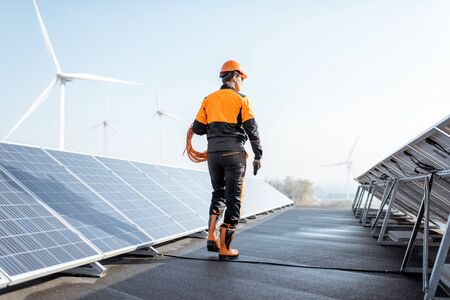Photo pour Well-equipped worker in protective orange clothing walking and examining solar panels on a photovoltaic rooftop plant. Concept of maintenance and installation of solar stations - image libre de droit
