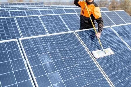 Photo pour Professional cleaner in protective workwear cleaning solar panels with a mob. Concept of solar power plant cleaning service - image libre de droit