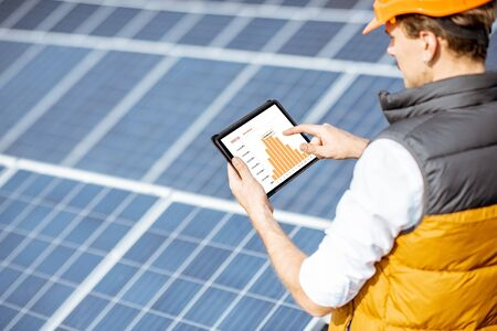 Photo for Man examining genaration of solar power plant, holding digital tablet with a chart of electricity production. Concept of online monitoring of the electric station - Royalty Free Image