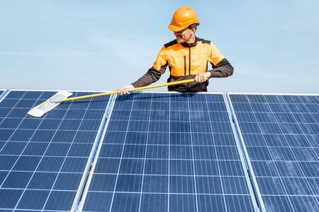 Photo for Professional cleaner in protective workwear cleaning solar panels with a mob. Concept of solar power plant cleaning service - Royalty Free Image
