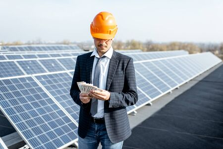 Photo for Portrait of a happy businessman with money earned from the electricity production of a solar station. Concept of successful investment in alternative energy - Royalty Free Image