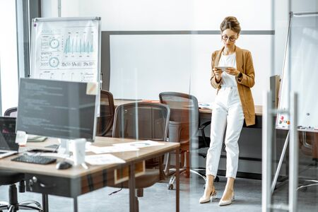 Photo pour Young business woman preparing for a presentation, standing alone with phone near flipchart in the modern office or coworking space - image libre de droit