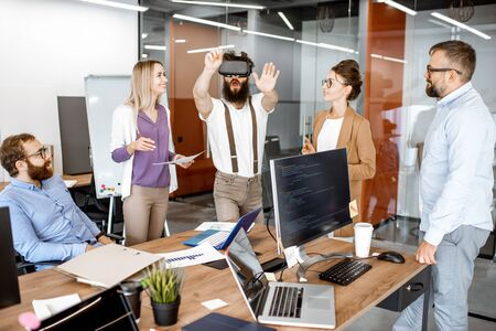Foto de Group of diverse colleagues during small conference in the office, creative bearded man trying a new product with virtual reality goggles - Imagen libre de derechos