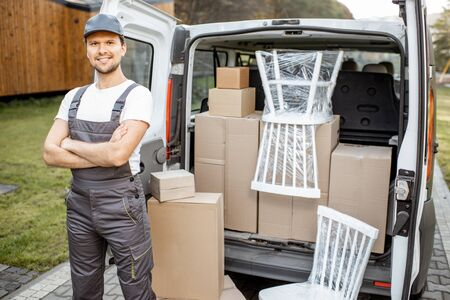 Photo for Portrait of a handsome delivery man in uniform standing near a cargo van vehicle trunk full of boxes and furniture during a relocation - Royalty Free Image