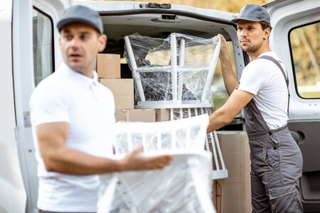 Photo for Delivery company employees unloading cargo van vehicle, delivering some goods and furniture to a clients home. Relocation and professional delivery concept - Royalty Free Image