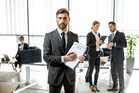 Photo pour Portrait of a bank employee with home loan agreement standing at the bank office with coworkers on the background - image libre de droit