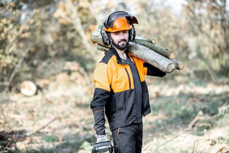 Photo pour Portrait of a professional lumberman in protective workwear with a chainsaw and wooden logs during the work on logging in the pine forest - image libre de droit