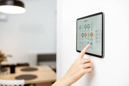 Photo pour Controlling home with a digital touch screen panel installed on the wall. Close-up on a screen with mobile application for managing smart devices - image libre de droit