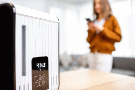 Foto de Close-up on a smart air humidifier with touch screen, woman controlling it with smart phone on the background - Imagen libre de derechos