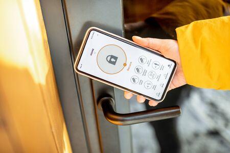 Foto de Locking smartlock on the entrance door using a smart phone remotely. Concept of using smart electronic locks with keyless access - Imagen libre de derechos