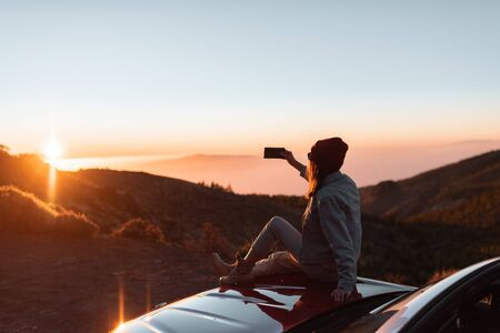 Photo for Young woman photographing with phone beautiful landscape during a sunset, sitting on the car hood while traveling high in the mountains - Royalty Free Image
