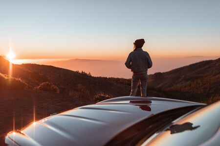 Photo pour Landscape view on the roadside above the clouds with woman enjoying beautiful sunset while traveling on the convertible sports car - image libre de droit