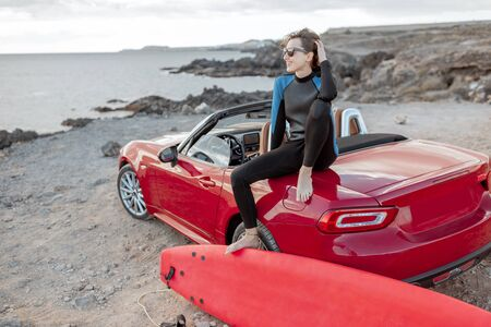 Photo pour Portrait of a young woman surfer in swimsuit sitting with surfboard on the red cabriolet on the rocky ocean coast. Active lifestyle and surfing concept - image libre de droit