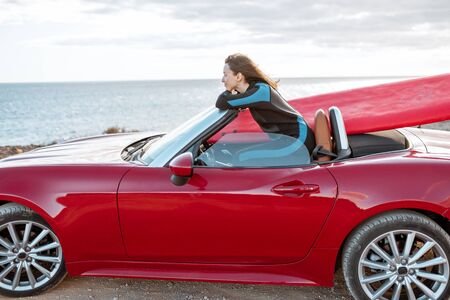 Photo pour Woman enjoying beautiful landscapes while sitting on her sports car with a surfboard near the ocean. Carefree lifestyle and active sports concept - image libre de droit