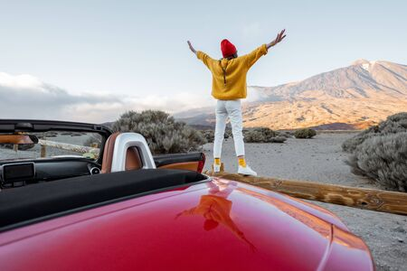Photo pour Woman dressed in bright sweater and hat enjoying great mountain landscapes while standing back on the road fence. Traveling by car on Tenerife island, wide view - image libre de droit