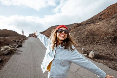 Photo for Lifestyle portrait of a carefree stylish woman enjoying a trip on a rocky coast, having fun while walking on the desert road. Happy travel and freedom concept - Royalty Free Image