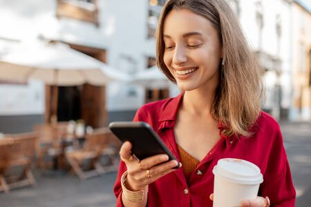 Photo pour Lifestyle portrait of a young stylish woman in red shirt with coffee cup and smart phone walking on the street in the old city - image libre de droit