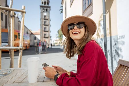 Photo pour Young stylish woman feeling happy and calm, while resting on the cafe terrace in the old city street. Traveling in La Laguna city on Tenerife island - image libre de droit