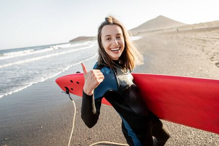 Photo pour Portrait of a young joyful woman in wetsuit carrying surfboard on the ocean beach during a sunset. Water sport and active lifestyle concept - image libre de droit