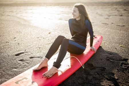 Photo pour Portrait of a young relaxed surfer in wetsuit sitting with surfboard on the beach. Water sport and active lifestyle concept - image libre de droit