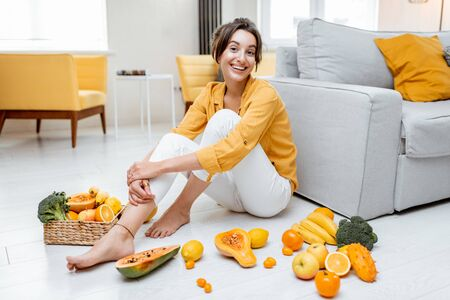 Photo pour Portrait of a young and cheerful woman sitting with lots of fresh fruits and vegetables on the floor at home. Photo carried in yellow color. Concept of wellbeing, healthy food and homeliness - image libre de droit
