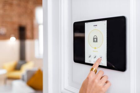 Photo for Controlling home alarm system with a digital touch screen panel installed on the wall. Concept of wireless secure control and smart home - Royalty Free Image