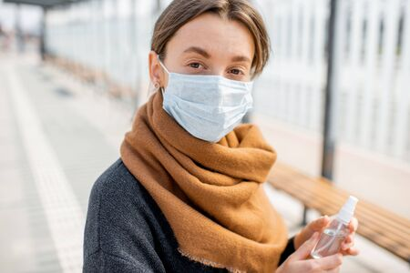 Photo pour Portrait of a young depressed woman in face mask during an epidemic outdoors. Concept of social isolation during Coronavirus epidemic - image libre de droit