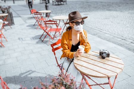Photo pour Young woman in facial mask sitting on the cafe terrace alone. Concept of social distancing and new social rules after coronavirus pandemic. - image libre de droit