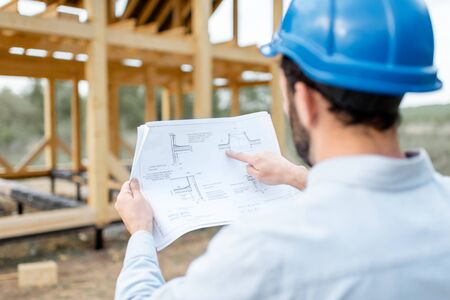 Photo pour Builder looking on teh drawings of wooden house structures on the construction site. Concept of building and designing wooden frame house - image libre de droit