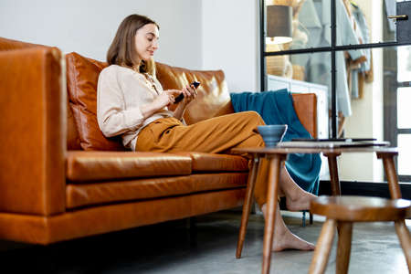 Photo pour Woman sitting on the sofa at home with smartphone - image libre de droit