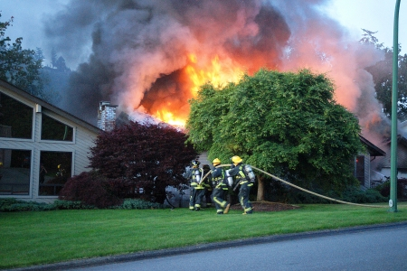 Firefighter fighting with fire burning house