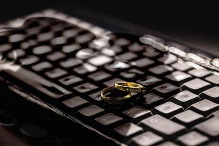 Photo pour Concept of infidelity or virtual betrayal. Golden wedding rings on a personal computer keyboard, with a double shadow on the rings. - image libre de droit