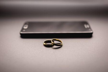 Photo pour golden wedding rings on a mobile phone. Concept of infidelity or virtual betrayal through the smartphone. - image libre de droit