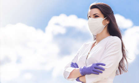 Photo pour A beautiful brunette girl in a medical suit, a protective mask on her face and gloves posing against a background of blue sky and clouds. The girl stands with crossed arms and looks into the distance. Horizontal photo - image libre de droit