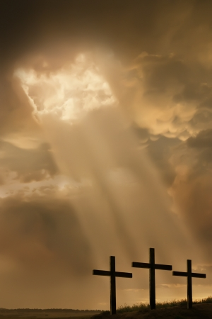 Inspirational religious photo illustration of three large crosses on the top of a hill a br