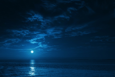 This photo illustration of a deep blue moonlit ocean at night with calm waves would make a great travel background for any coastal region or vacation, emphasizing the beauty of the night time ocean or sea